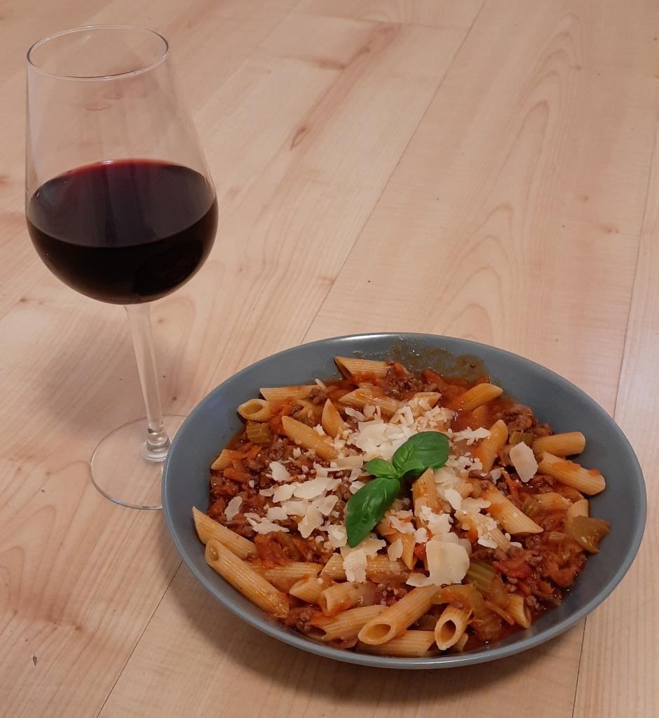 Talerz z makaronem z sosem bolońskim i kieliszek wina
