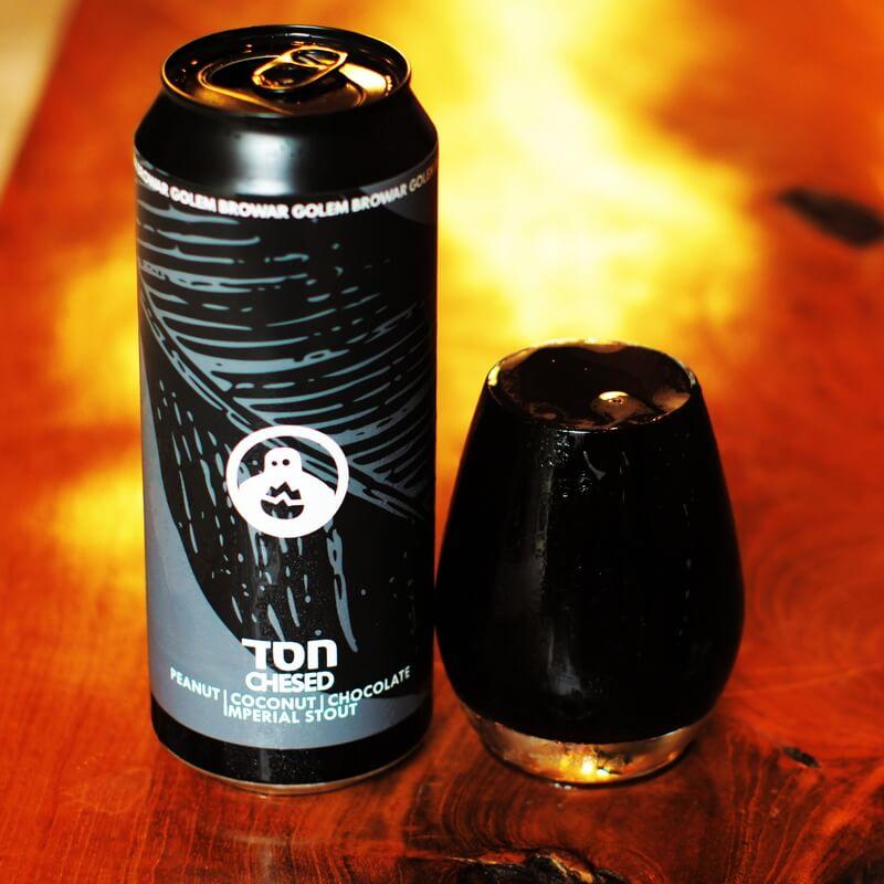 Puszka piwa Chesed i wypełnione po brzegi szkło ciemnym piwem